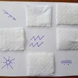 Ant lapo nupiešiau keletą ženklų, juos užklojau popierinio rankšluosčio kvadratėliu, kad uždengtų piešinuką.