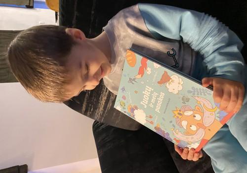 Vaikas kuris labai džiaugiasi knyga